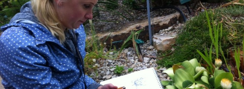 Mature student sitting in the Great Glasshouse sketching one of the plants